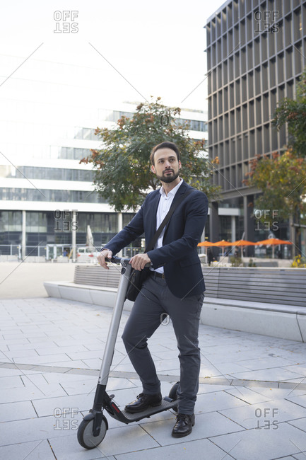 Male business person with electric scooter against building in city