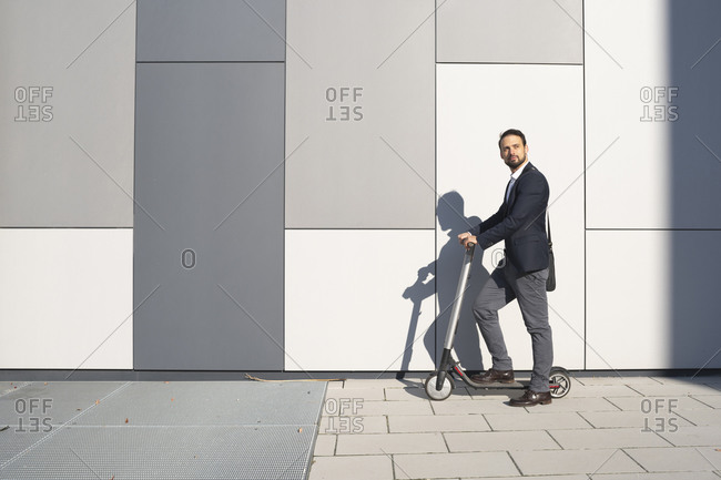 Businessman riding on electric scooter against wall in city