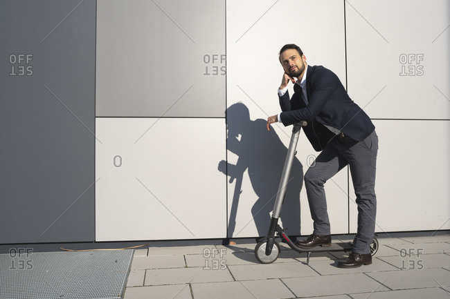 Confident entrepreneur looking away while leaning on electric push scooter in city