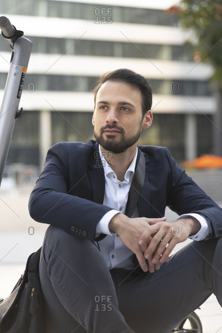 Confident businessman on electric push scooter sitting in city