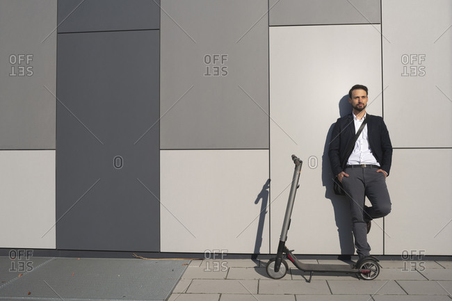 Confident entrepreneur looking away while standing by electric push scooter against wall