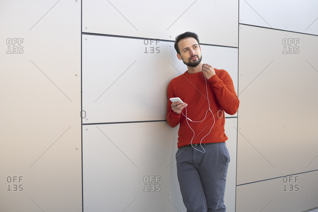 Contemplating entrepreneur with in-ear headphones standing against wall