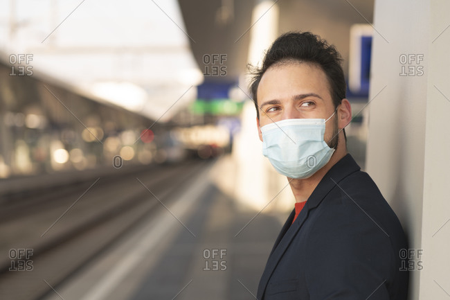 Male entrepreneur looking away while wearing protective mask on railroad platform