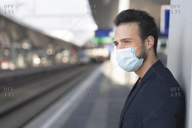 Male entrepreneur looking away while wearing protective mask on railroad station platform