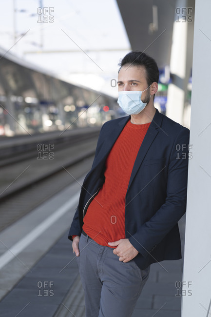 Male entrepreneur wearing protective mask while looking away on railroad station platform