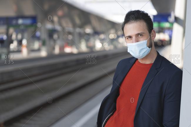 Male entrepreneur wearing protective mask on railroad station platform