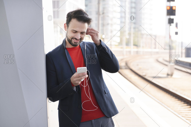 Smiling entrepreneur with in-ear headphones standing on railroad platform
