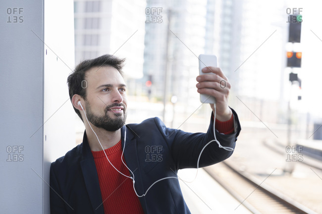 Smiling entrepreneur with in-ear headphones standing by wall on railroad platform