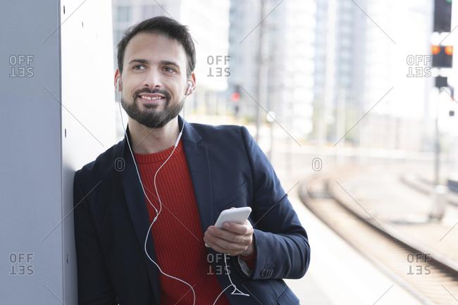 Smiling entrepreneur with in-ear headphones waiting on railroad platform