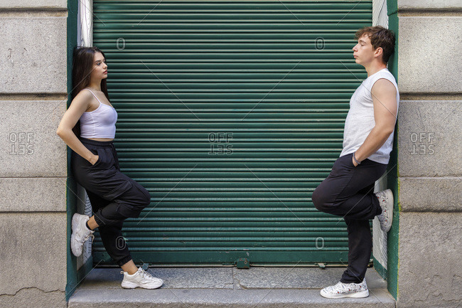 Young man and woman leaning on wall against shutter