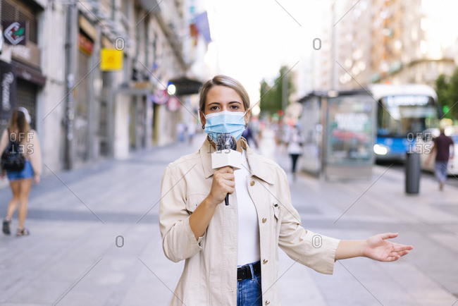 Female reporter wearing mask talking over microphone on street in city