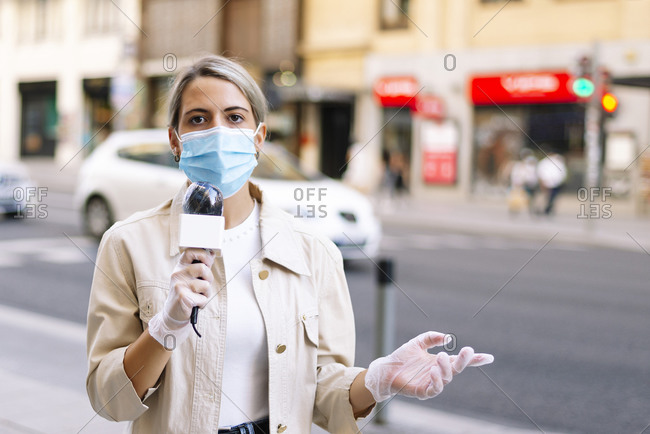 Female reporter wearing mask talking over microphone while standing on street in city