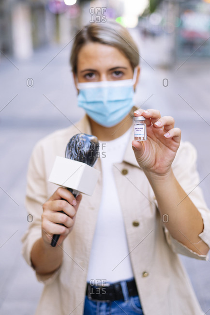 Female journalist wearing mask showing vaccine while standing on street in city