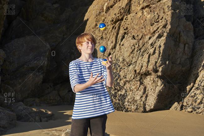 Boy juggling balls while playing at beach
