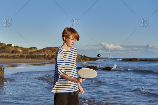 Boy playing with ball and racket while standing at against sea