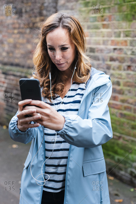 Mid adult woman photographing through mobile phone while standing in city