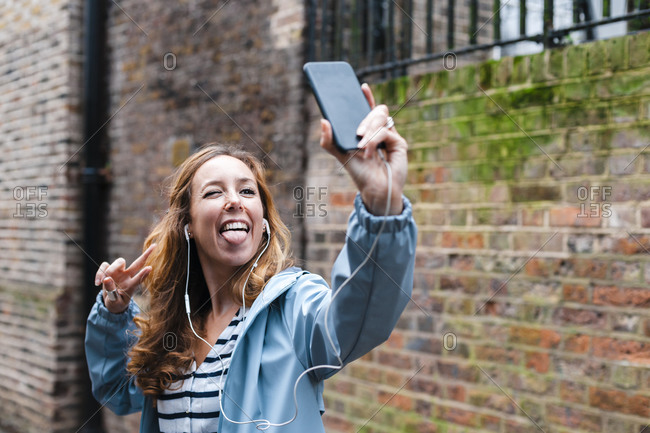 Carefree woman with in-ear headphones sticking tongue out while taking selfie through mobile phone in city