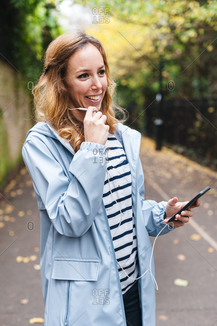 Smiling woman talking on mobile phone while exploring city