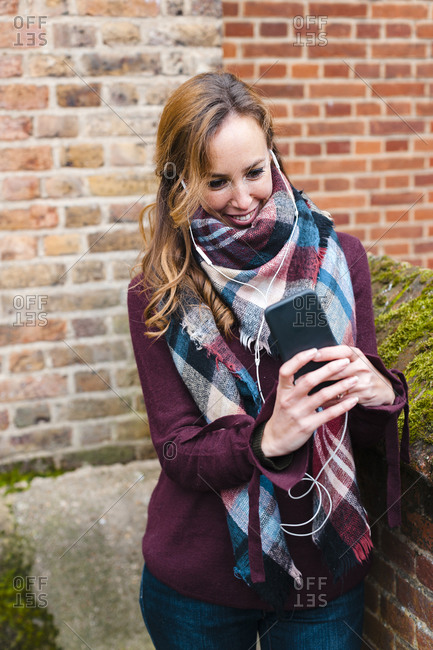 Woman with in-ear headphones using smart phone while standing against brick wall
