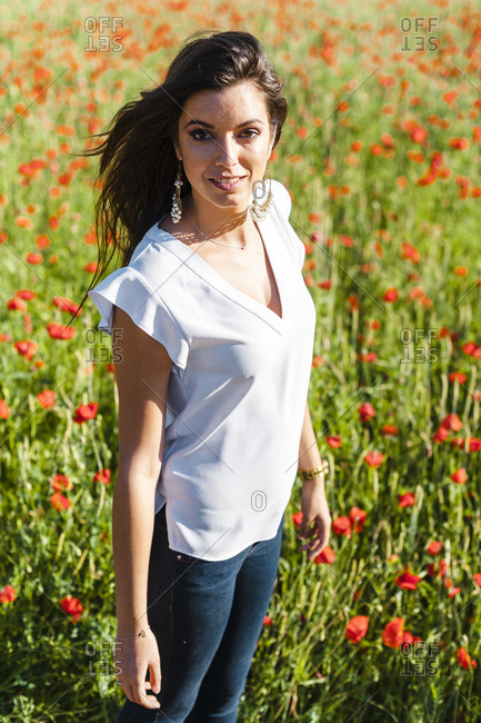 Smiling beautiful woman standing at poppy field during springtime