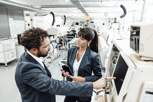 Businessman pointing at computer monitor while businesswoman holding digital tablet in industry