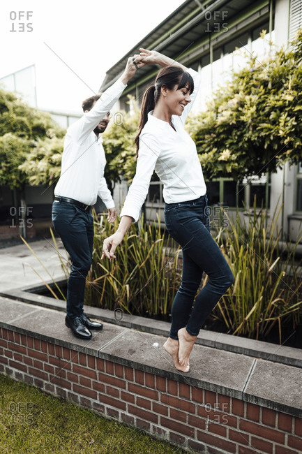 Carefree colleagues dancing on retaining wall outside industry