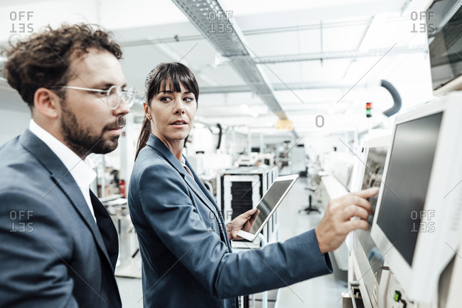 Confident businesswoman pointing at computer monitor while looking at businessman in industry