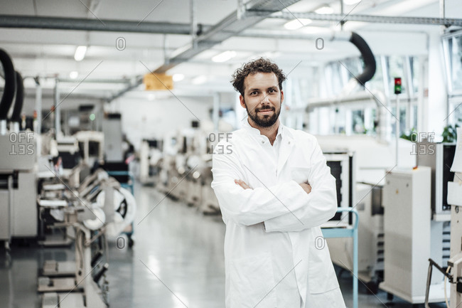 Male scientist wearing lab coat while standing with arms crossed at bright laboratory
