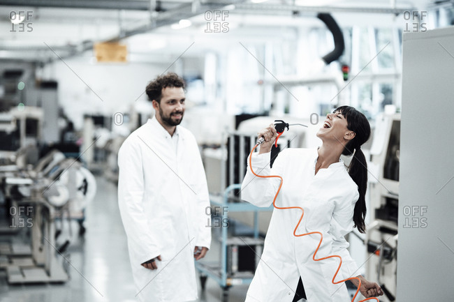 Cheerful female scientist enjoying breakthrough research results while male colleague watching her