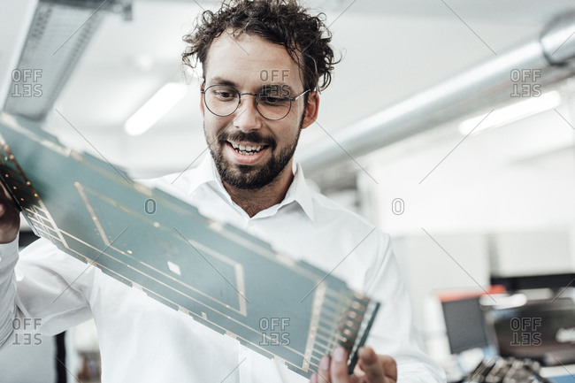 Smiling male engineer examining large computer chip in industry