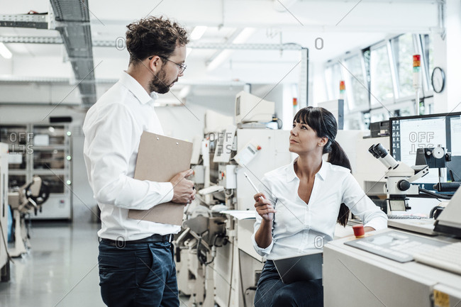 Confident female technician discussing with male colleague at laboratory