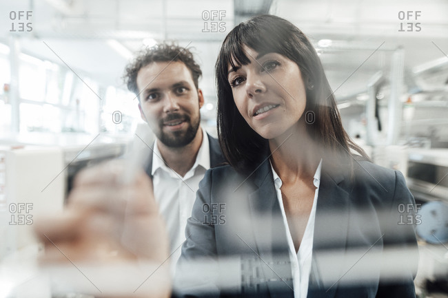 Confident businesswoman planning with businessman at industry