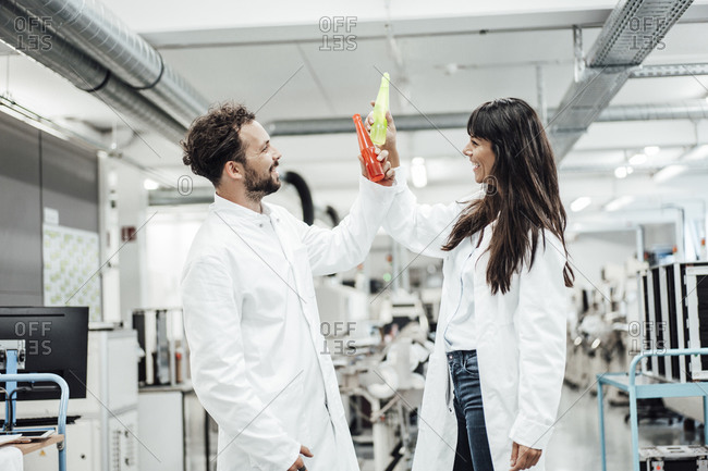 Happy male and female technicians toasting drinks while standing in laboratory