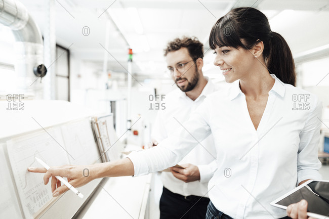 Smiling female technician pointing at graph while discussing with male colleague at laboratory