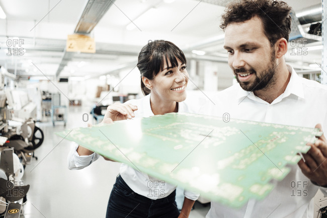 Smiling male and female technicians analyzing large computer chip in industry
