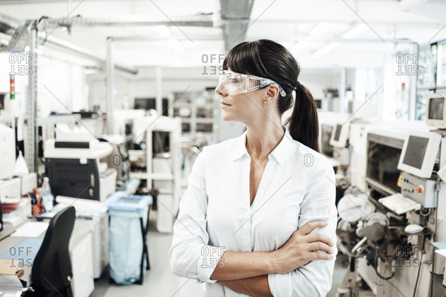 Thoughtful female technician looking away while standing with arms crossed in industry