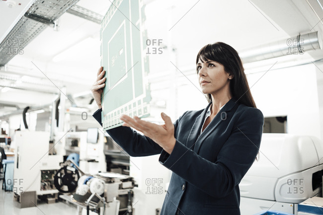 Confident businesswoman analyzing large computer chip in industry