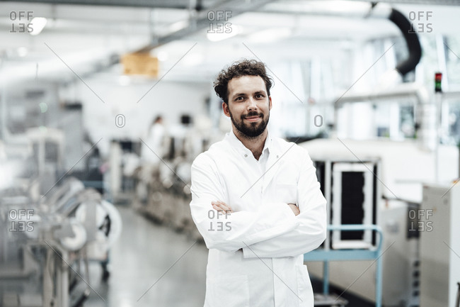 Confident male scientist in white lab coat while standing with arms crossed at bright laboratory