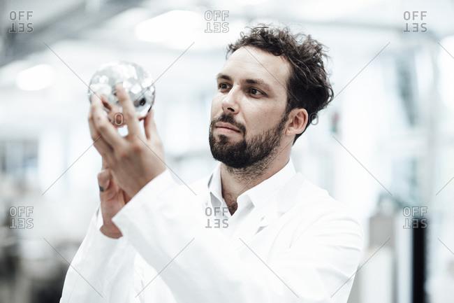 Male technician analyzing shiny sphere at laboratory