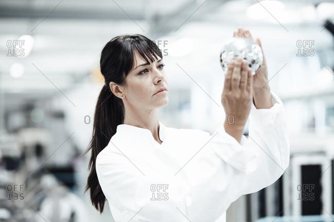 Confident female technician analyzing shiny sphere at laboratory