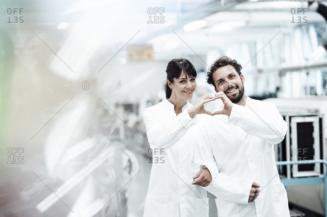 Smiling male and female scientists making heart shape with hands while standing arm in arm at laboratory