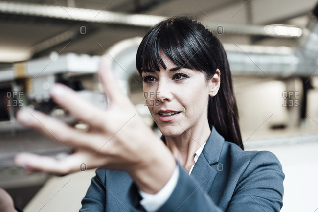 Female professional investigating machine part at industry