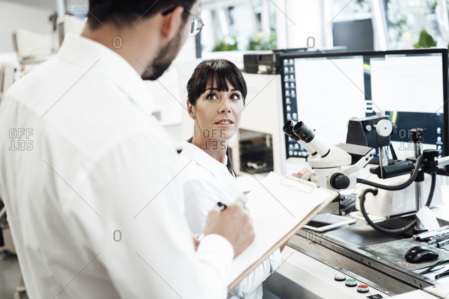 Businesswoman looking at businessman standing with clipboard in laboratory