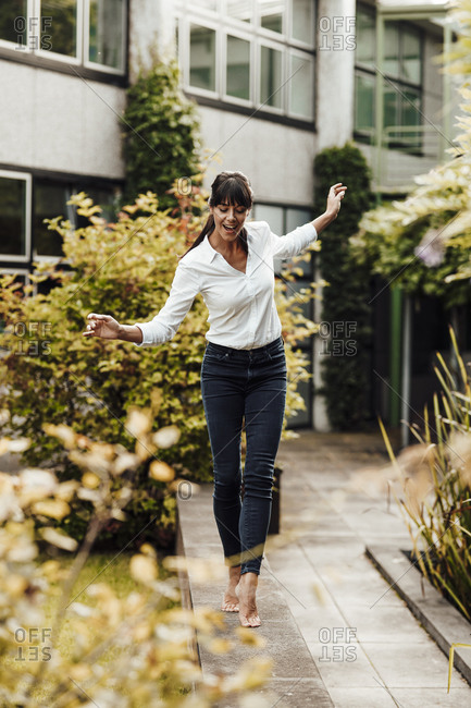 Smiling carefree female professional walking on retaining wall at industry