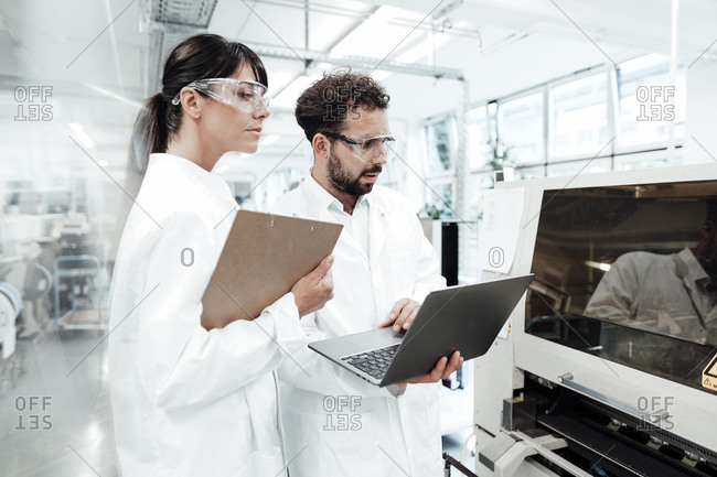 Male and female scientists with laptop and clipboard looking at machinery in laboratory