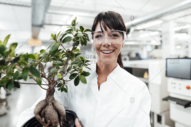 Smiling female scientist holding potted plant at laboratory