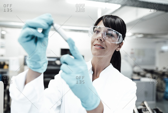 Smiling mature female scientist looking at sample in laboratory