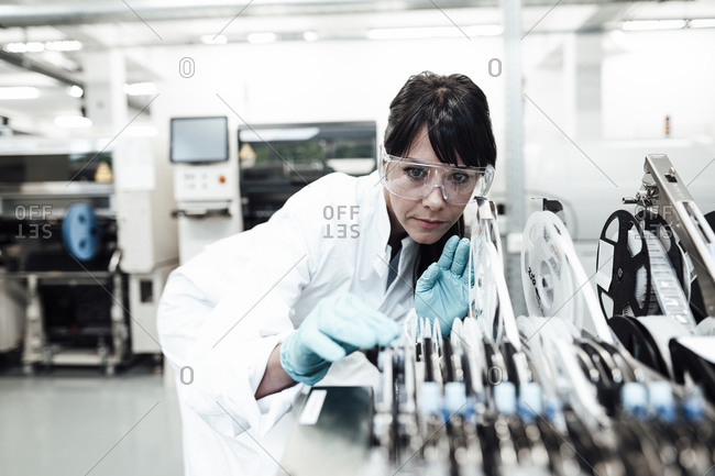 Mature female technician examining machinery in bright industry
