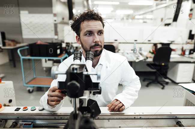 Male scientist looking away while sitting with microscope in bright laboratory