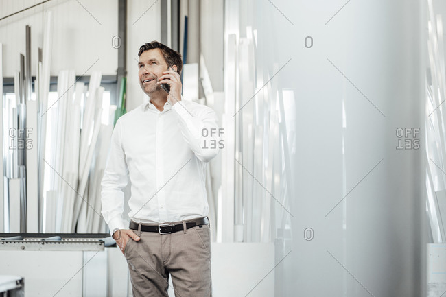 Male manager talking on smart phone while standing with hand in pocket at industry
